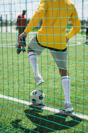 goalkeeper stopping ball during soccer match on pitch