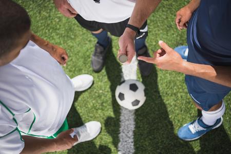 ピッチのサッカーの試合の開始前に、コインを保持している審判 写真素材
