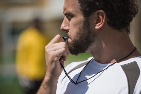 voetbalscheidsrechter fluit in fluitje op voetbalveld tijdens het spel