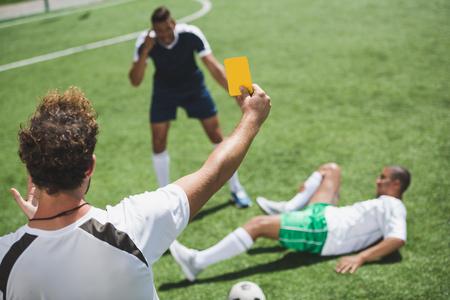 voetbalscheidsrechter die gele kaart toont aan spelers tijdens spel