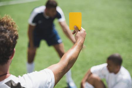 축구 심판 게임 도중 선수들에게 옐로 카드를 보여주기 스톡 콘텐츠