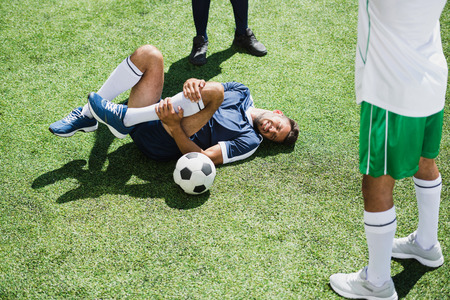 injured soccer player lying on football field Stock Photo