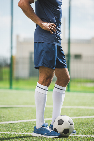 soccer player standing on soccer pitch with ball