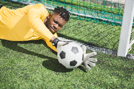 african american goalkeeper catching ball during soccer match