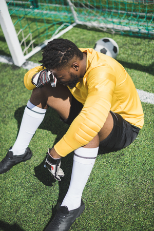african american goalkeeper sitting at goalpost on pitch