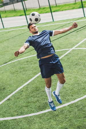 athletic soccer player training with ball on soccer pitch
