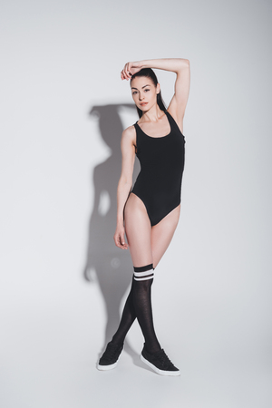 young brunette woman in black leotard posing and looking at camera on grey