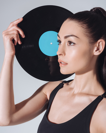 young brunette woman holding vinyl record and looking away isolated on grey