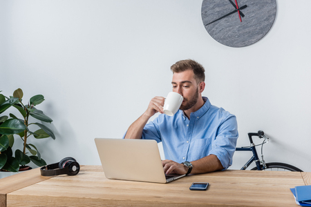 young businessman drinking coffee while working in office