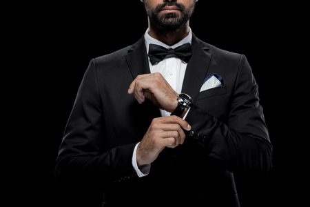 businessman in bow tie and tuxedo with watch, isolated on black Banco de Imagens