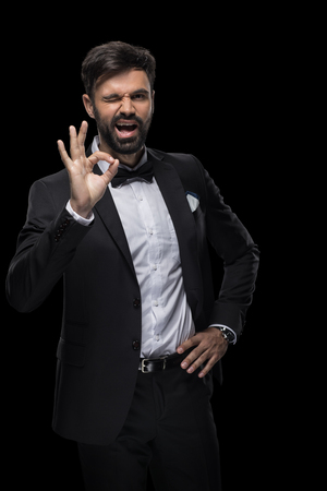 handsome bearded businessman in bow tie winking and showing ok sign 版權商用圖片