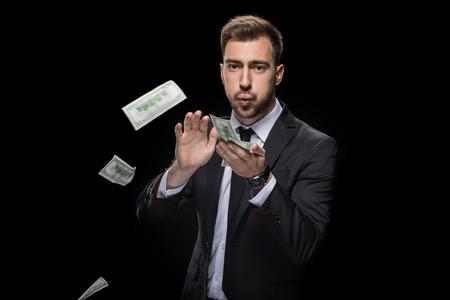 handsome rich businessman throwing dollar banknotes