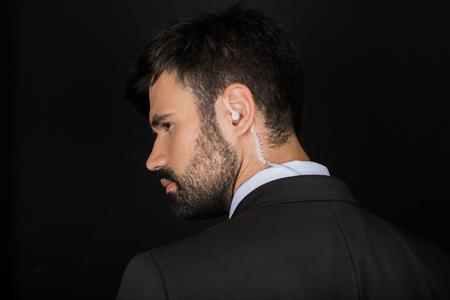 Secret service agent in suit using earphone