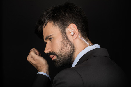 Geheime service agent in kostuum met behulp van oortelefoon Stockfoto