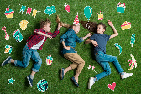 Happy three friends lying on grass Stock Photo