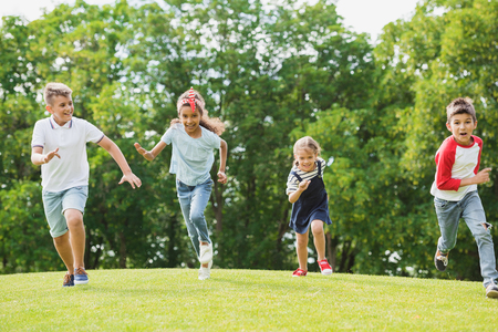 happy multiethnic kids playing and running together on green grass in park