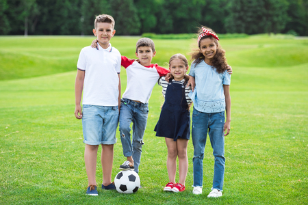 multiethnic kids standing with soccer ball and smiling at camera in park