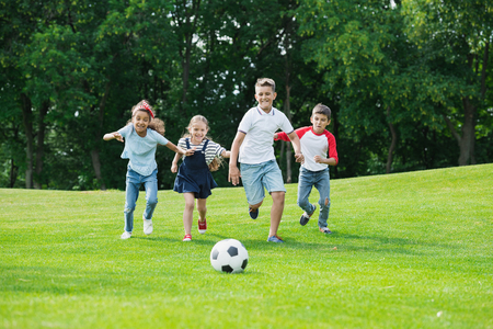 happy multiethnic kids playing soccer with ball in park