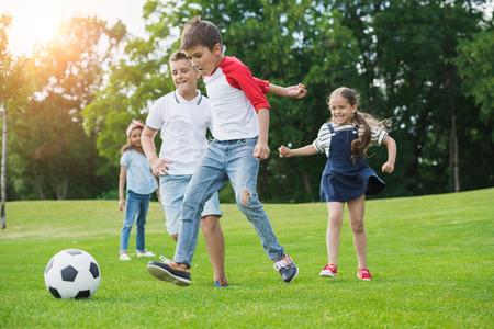 公園でボールとサッカー幸せな多民族の子供たち