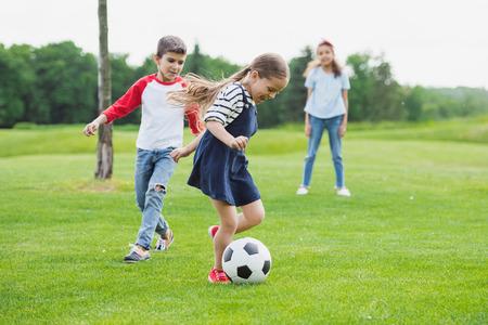 Crianças alegres jogando futebol com bola em grama verde Foto de archivo - 84434759