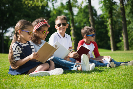 multiethnic kids in sunglasses reading books in park