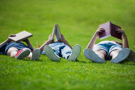 Children lying on grass together and reading books