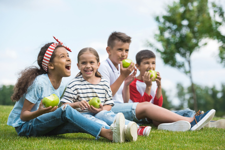 multiethnic children eating green apples while sitting together on green grass Reklamní fotografie
