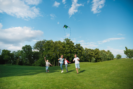 multiethnic kids playing together while running with kite in park Stock Photo - 84373009