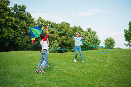 multiethnic kids playing with kite on green lawn in park
