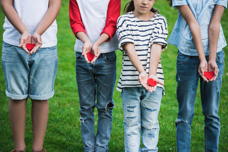 cute little children holding red hearts while standing on green grass