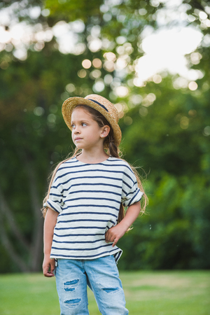 little girl in straw hat standing with hand on waist and looking away in park