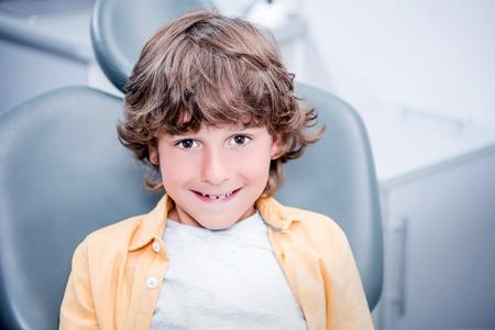 歯科医のオフィスの椅子に座っている少年の笑顔 写真素材 - 84441387