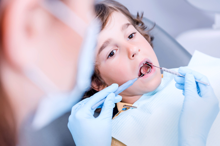 dentist examining teeth of little boy in dentist office Stock Photo