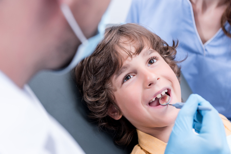 dentist examining teeth of little boy Stock Photo