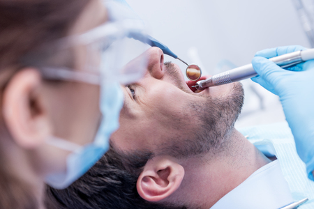 dentist in protective mask and glasses curing teeth of patient