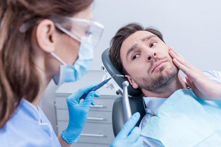 patient looking at dentist in protective mask with dental tools in hands