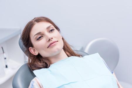 歯科医院の椅子に座っている美しい女性 写真素材