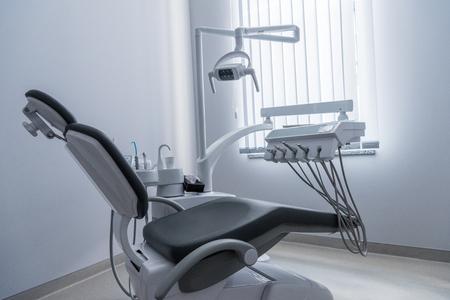 Zahnarztpraxis mit Stuhl und verschiedenen zahnmedizinischen Geräten