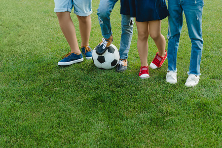 children standing with soccer ball on green grass