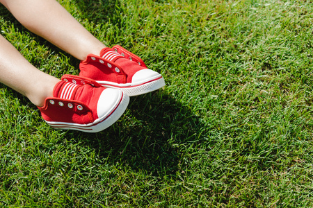 little feet in red sneakers on green grass