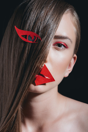 woman with long hair and bright paper makeup posing for fashion shoot