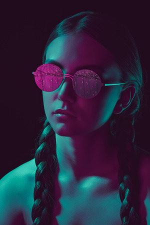 thoughtful young woman in stylish round sunglasses