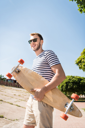 smiling young man in sunglasses holding skateboard and looking away