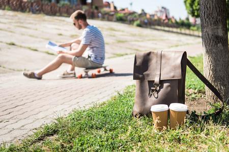 brown leather shoulder bag with disposable coffee cups and man sitting on skateboard behind