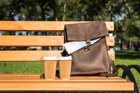 지도와 일회용 커피 컵 나무 벤치에 갈색 가죽 가방 스톡 콘텐츠