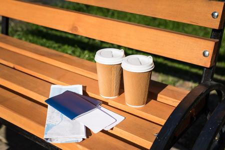 Passeports avec billets, carte et tasses à café jetables sur un banc en bois Banque d'images - 84440145