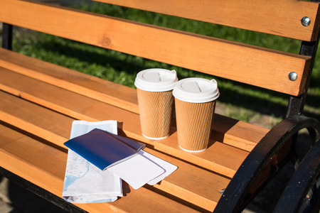 passports with tickets, map and disposable coffee cups on wooden bench 版權商用圖片