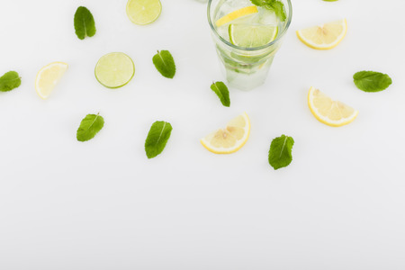 summertime drink with lime and lemon pieces and mint leaves isolated on white