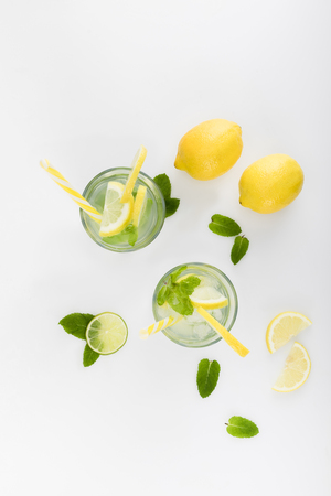 top view of refreshing lemonades with lime and lemon pieces