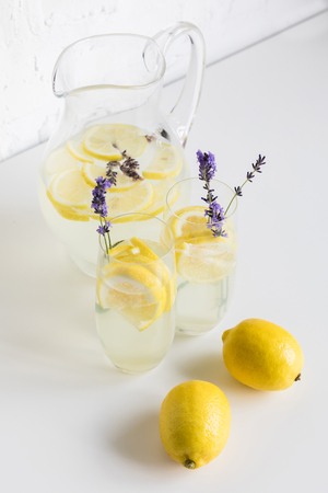 summertime lemonade with lavender and lemon pieces in glasses and jar